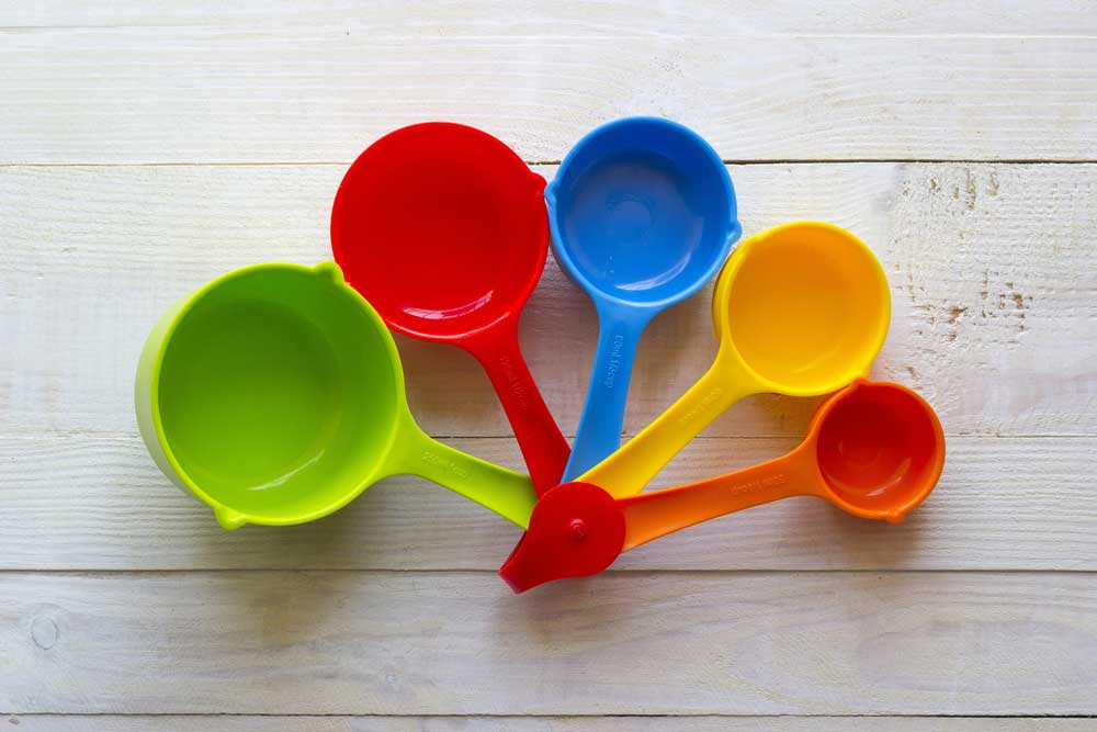 5 different size measuring cups in bright colors