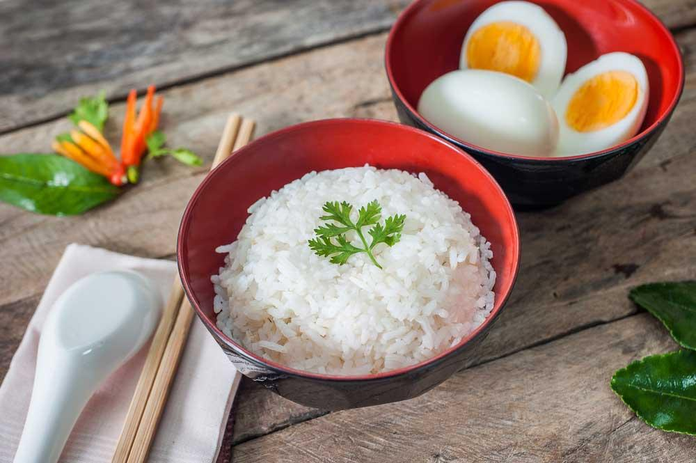 bowl of white rice with bowl of boiled eggs on wooden table top