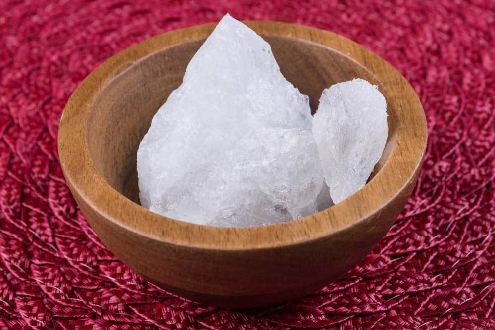 Styptic crystals in a wooden bowl on a red place mat