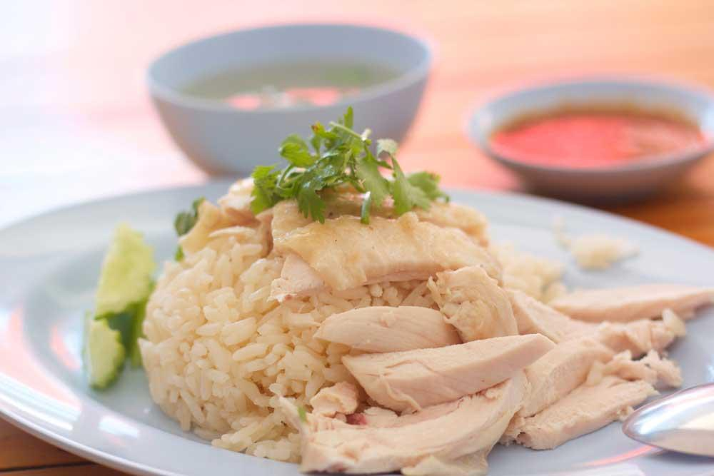 shredded chicken over scoop of rice with parsley garnish on white plate