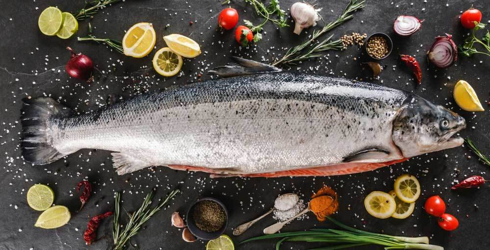 A whole Salmon on a stone counter top surrounded by herbs, lemons, tomatoes, garlic and onions
