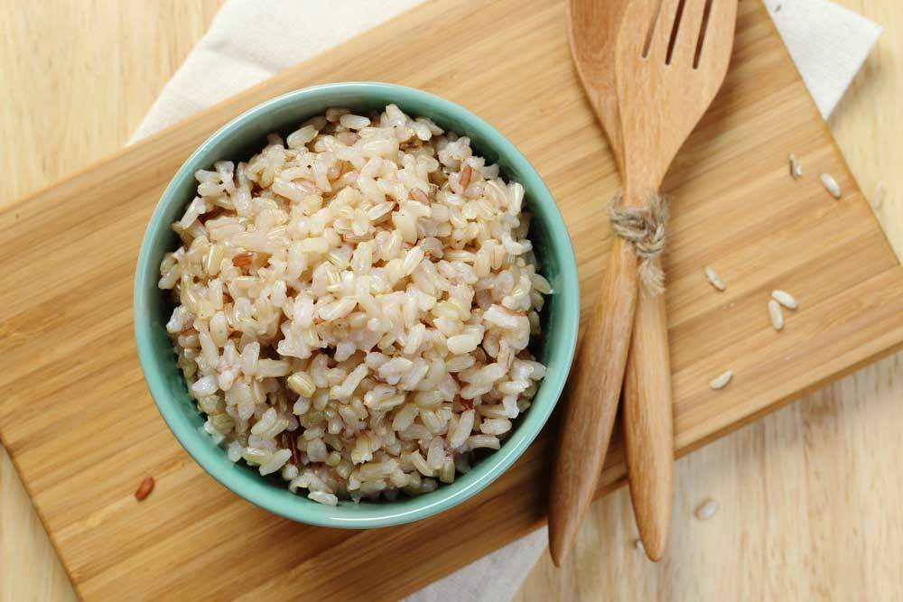 bowl of brown rice on a wooden cutting board with wooden spoon and fork