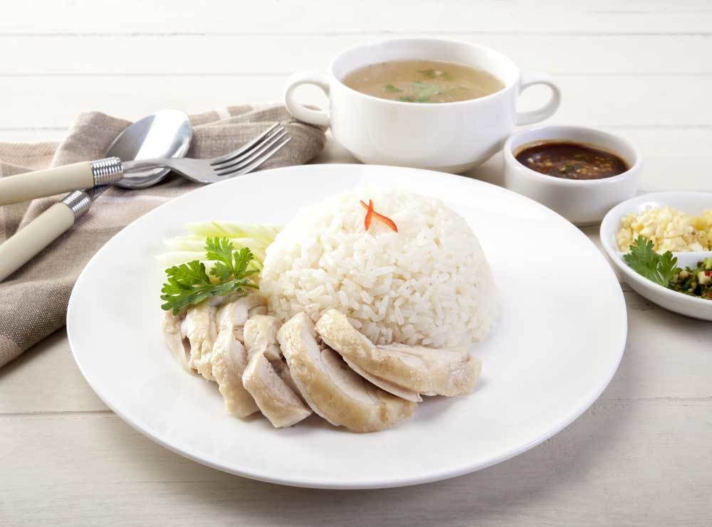 chicken and rice with garnish on white plate surrounded by smaller bowls and plates of food.