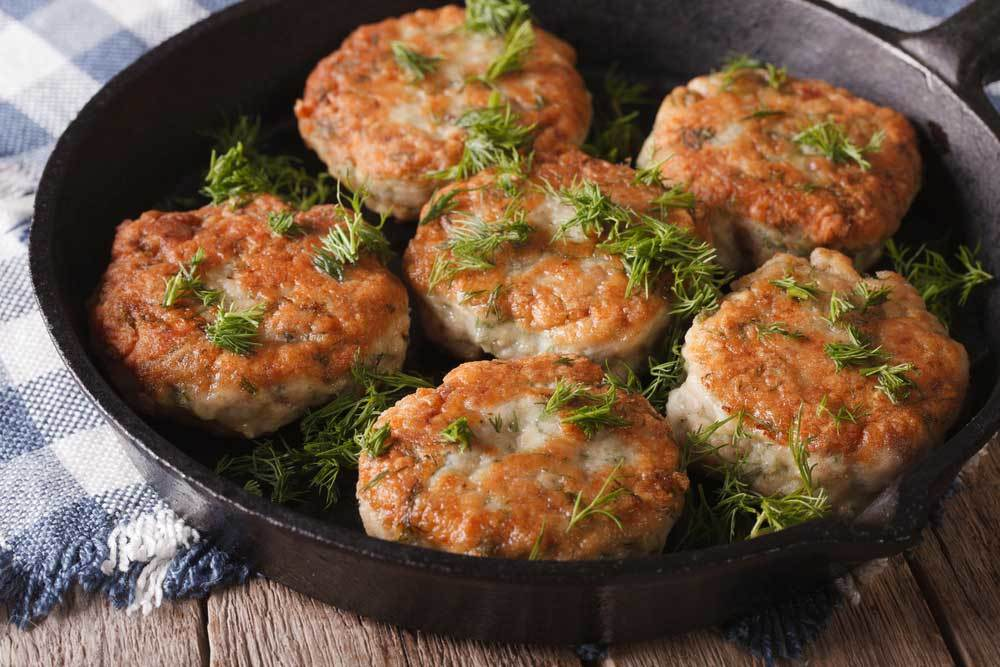 fish cakes in a cast iron skillet on a wooden table with a blue and white check tea towel.