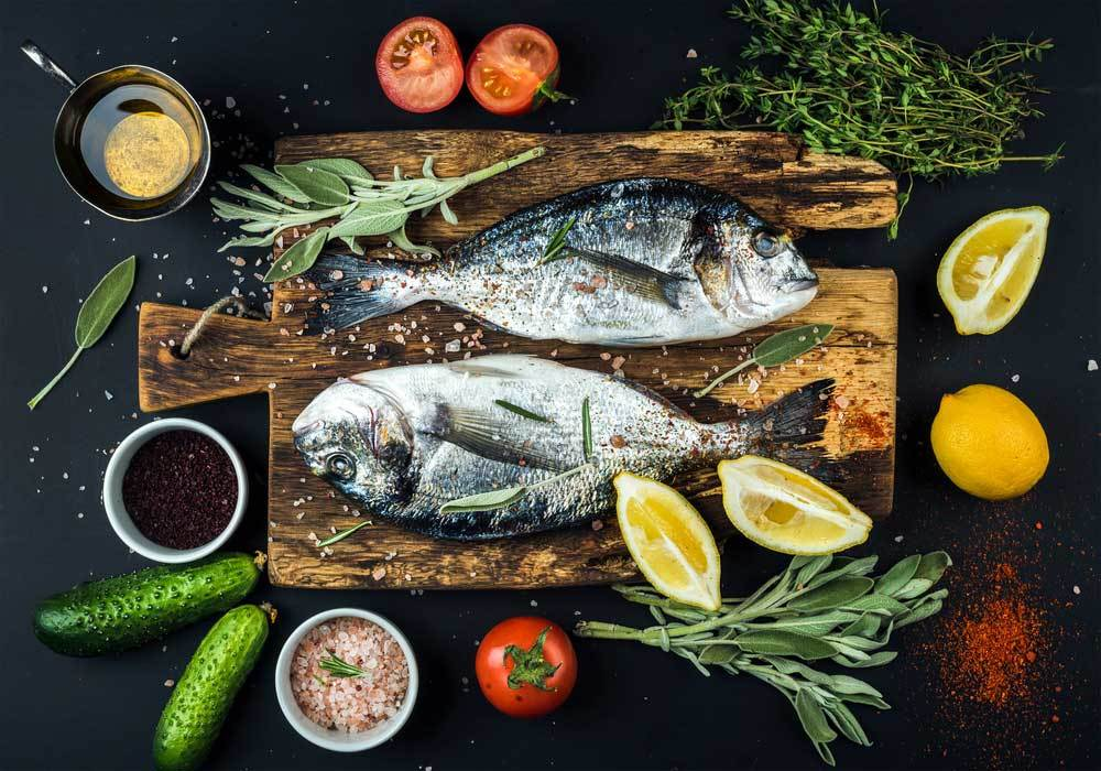 2 whole fish on a cutting board with herbs and vegetables