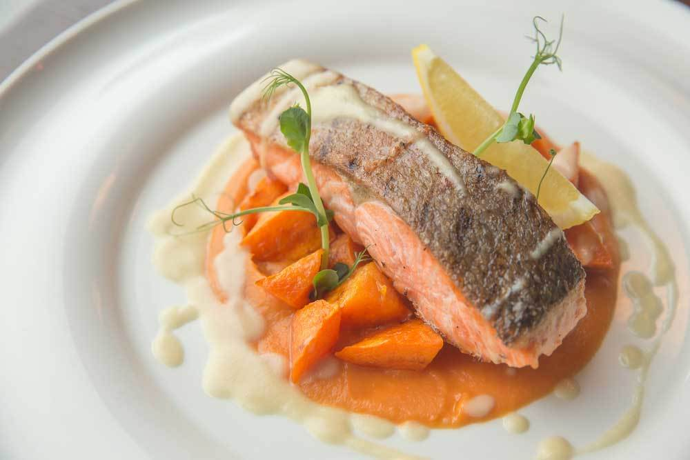 Cooked salmon steak over sweet potatoes with white sauce on a white plate with garnish