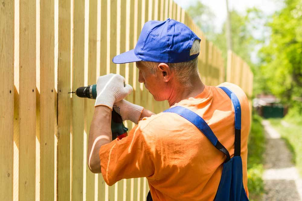 Man in overalls installing a wooden privacy fence