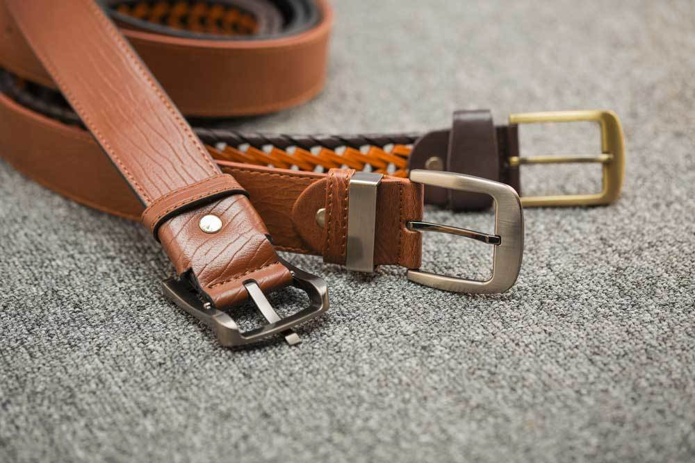 3 leather belts laying on a fabric covered surface