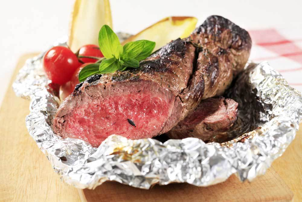 Piece of grilled beef and vegetables in aluminum foil