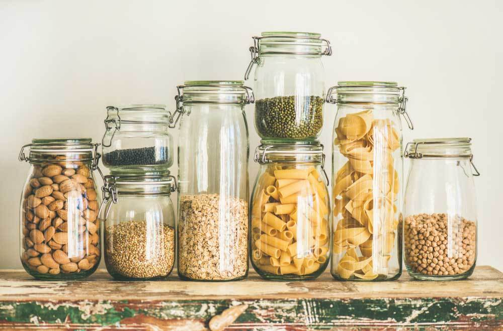 Variety of glass storage jars filled with pastas and grains on a shelf.