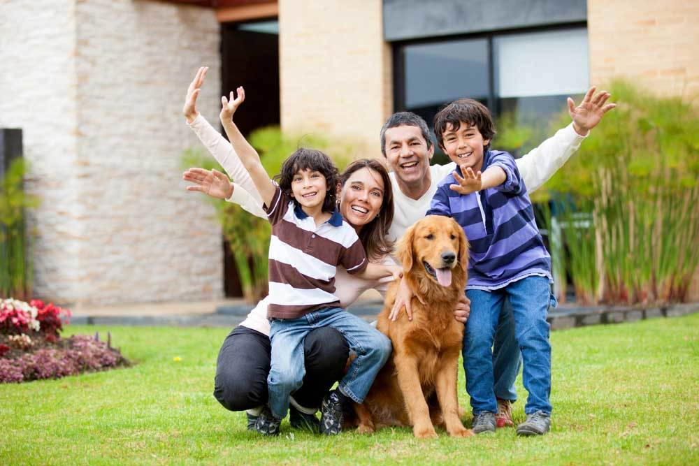 Family kneeling down in yard with dog