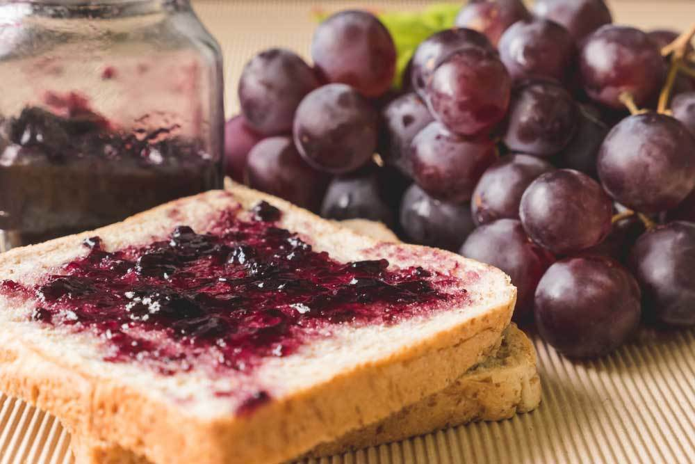 grape jelly on bread with a bunch of  grapes and a jar of jelly in background