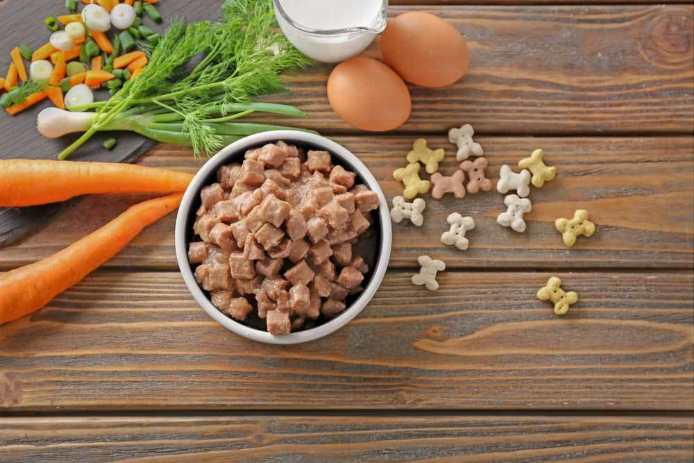 Wet dog food in metal bowl on wooden table surrounded by vegetables, milk, eggs, and dry kibble