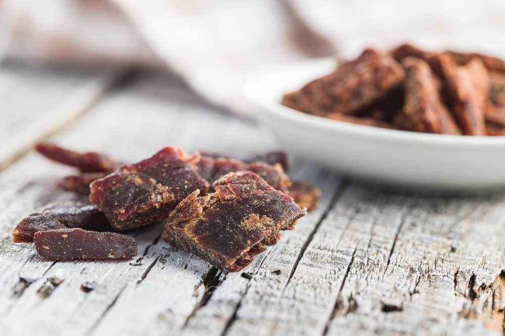 Pile of beef jerky on table in front of bowl of beef jerky.
