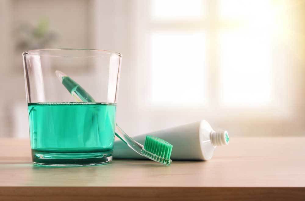 mouthwash in glass with toothbrush and toothpaste on counter