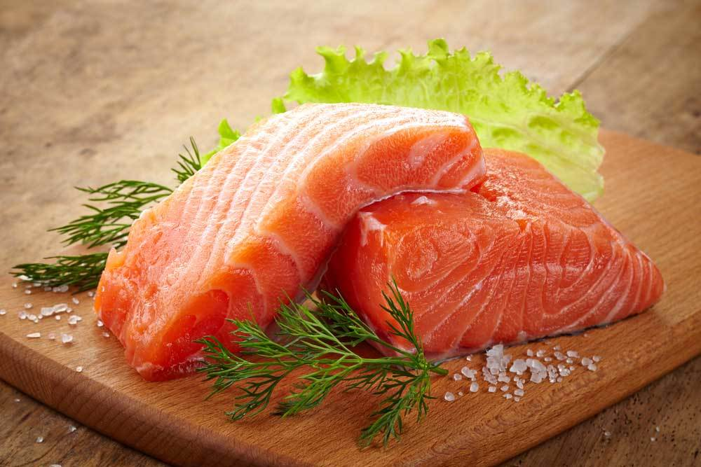 2 Salmon fillets with sprigs of dill and lettuce on a wooden cutting board.