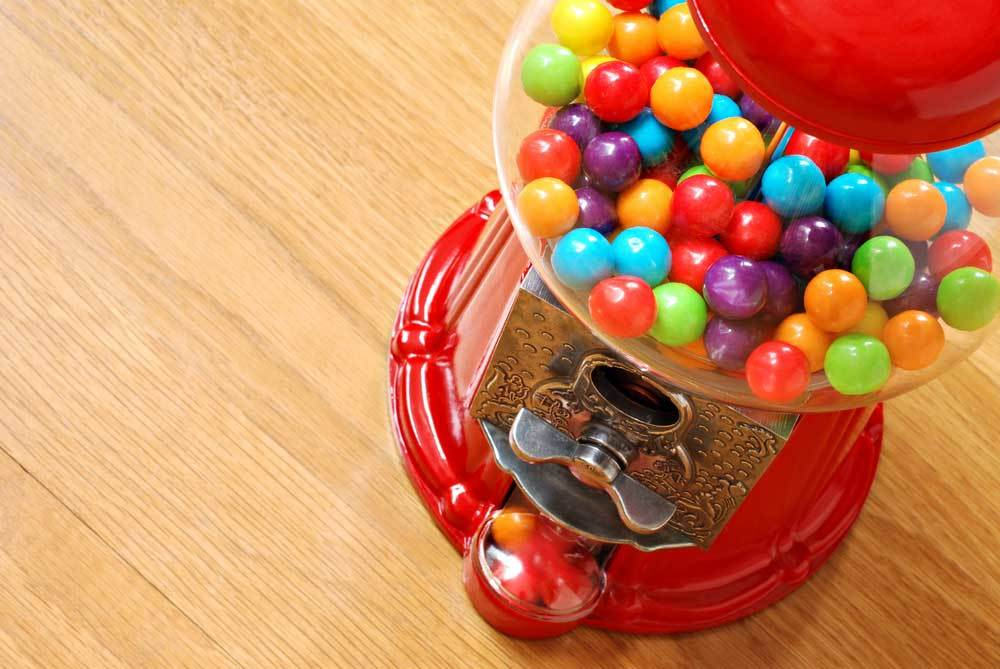 Red gumball machine half full of gumballs on a wooden counter