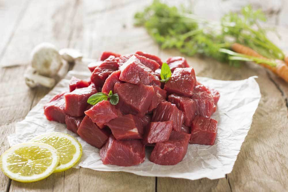 Raw beef stew meat on a piece of parchment on wooden table with 2 lemon slices and vegetables