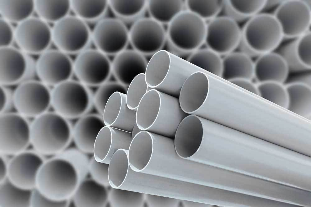 Stack of PVC pipe in background with 9 pieces of PVC pipe bundled in foreground