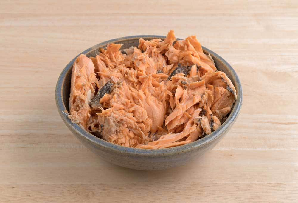 bowl of canned salmon on wooden table top