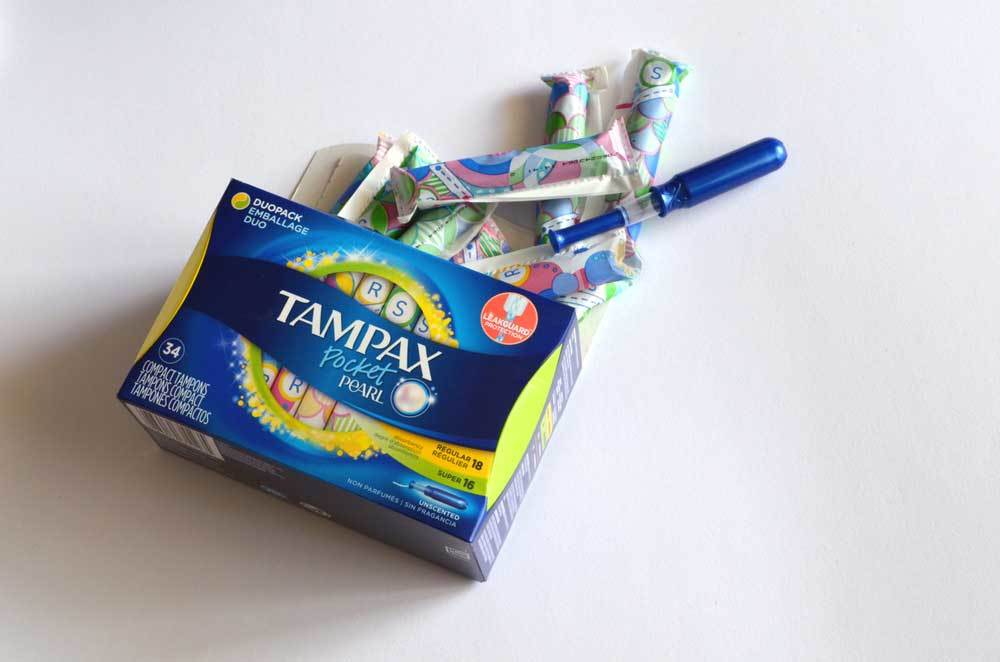 box of Tampax tampons spilled onto white surface