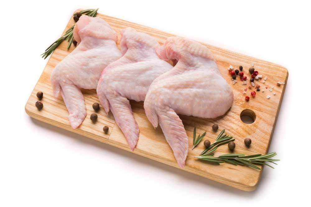 3 whole raw chicken wings on a cutting board surrounded by herbs and spices on a white background