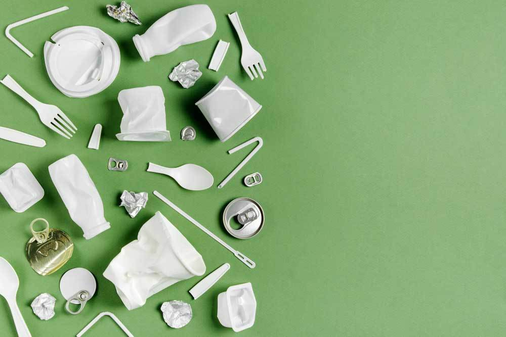Random items made from plastic and aluminum spread over half of a green background