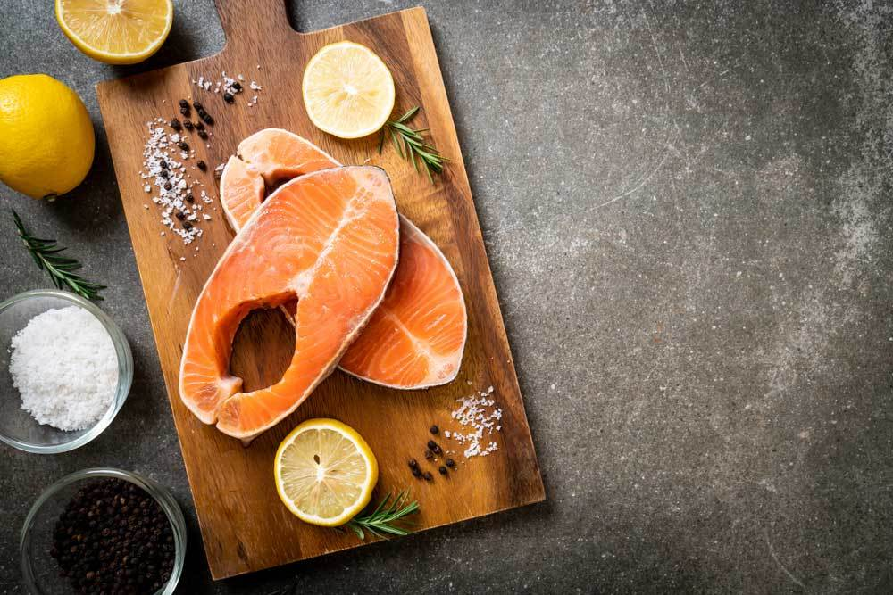 Salmon steaks on cutting board with herbs, spices and lemon slices