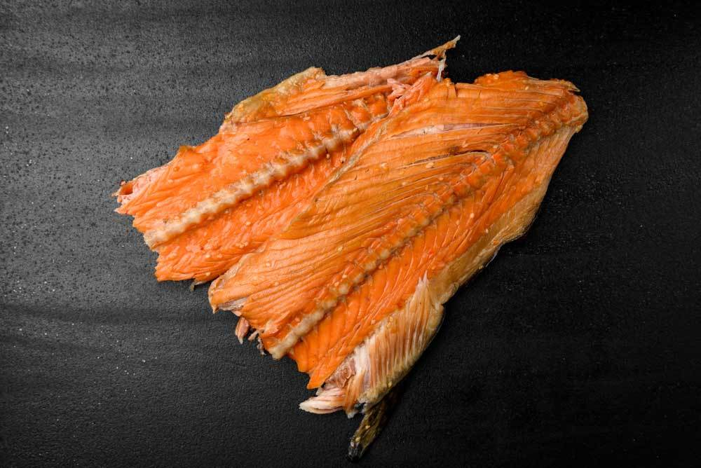 2 pieces of salmon with bones on black background