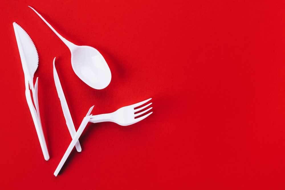broken plastic eating utensils on a red background