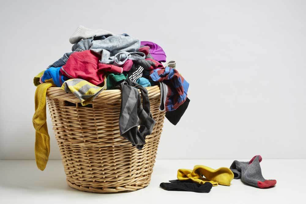 clothes basket full of clothes and socks with a few socks spilling onto floor