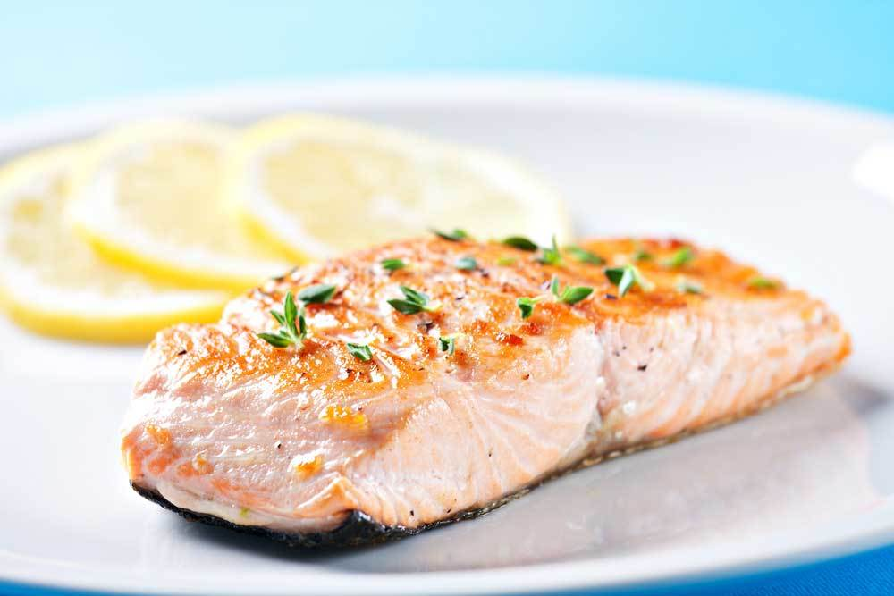 Cooked salmon fillet on white plate with lemon slices