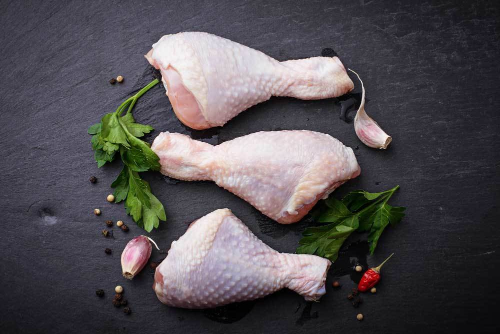 3 raw chicken drumsticks on a slate background with herbs, peppercorn and garlic