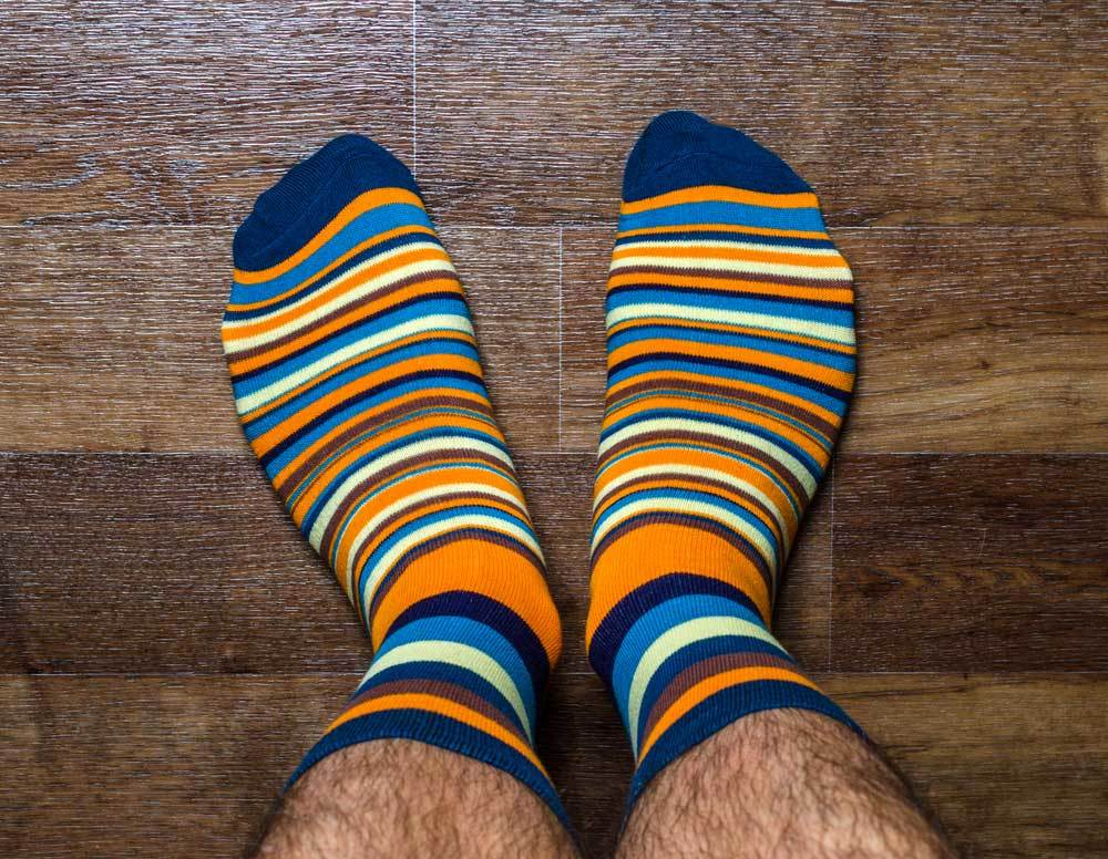 pair of mens feet wearing striped socks on hard wood floor