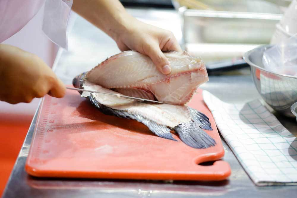fish being filleted on a cutting board