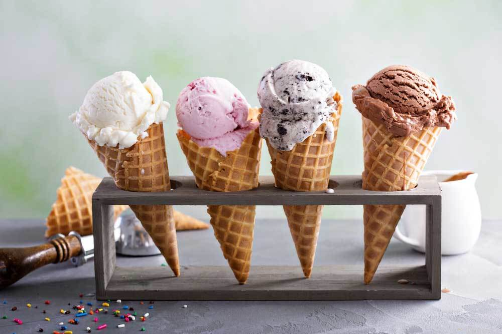 variety of flavored ice creams in cones standing in a cone holder