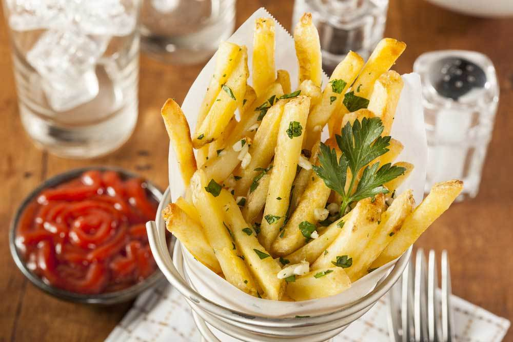 cone of garlic fries on table with fork and condiments