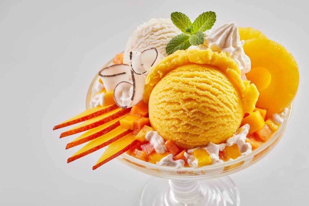 tropical fruits and ice cream in ice cream dish on white background