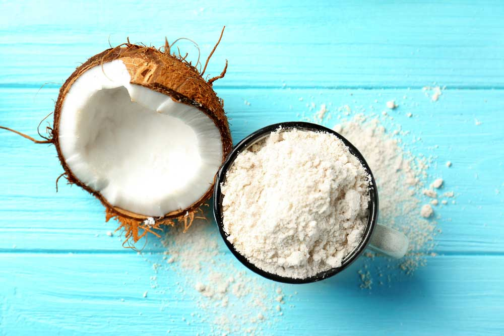 half of a coconut and a bowl of coconut flour on a bright blue table