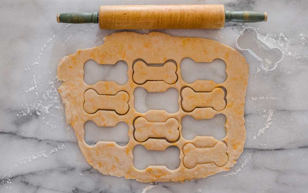 overhead view of dough rolled out onto a marble slab with a rolling pin and dog bone shapes cut out of the dough