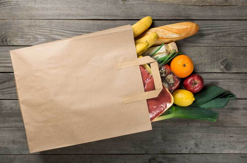 groceries spilling out of shopping bag onto wooden surface