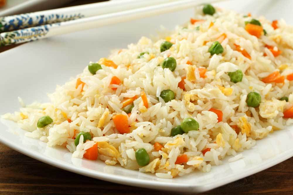 Chicken, vegetables and rice mixed together on  a white plate with chop sticks