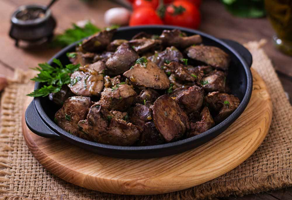 sauteed chicken livers in a black dish with parsley garnish