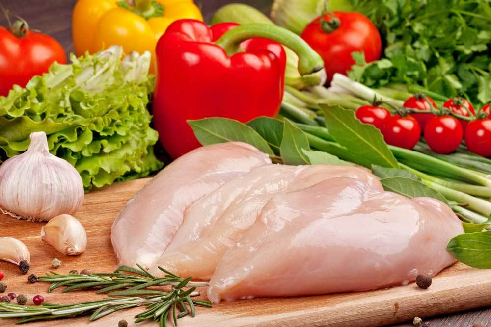 Raw chicken and vegetables on a cutting board