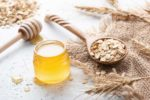jar of honey with a honey spoon, spoon of oats, and oat stalks laying on a piece of burlap