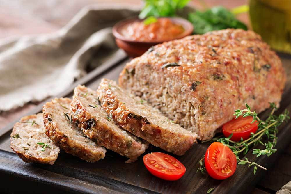 meatloaf on a cutting board surrounded by herbs and tomatoes