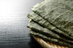 Nori sheets on a wicker plate on wooden surface