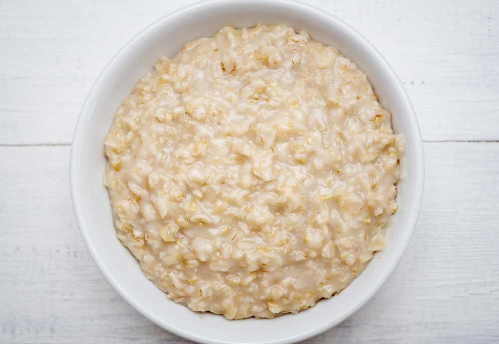 white bowl with oatmeal on a white wood table