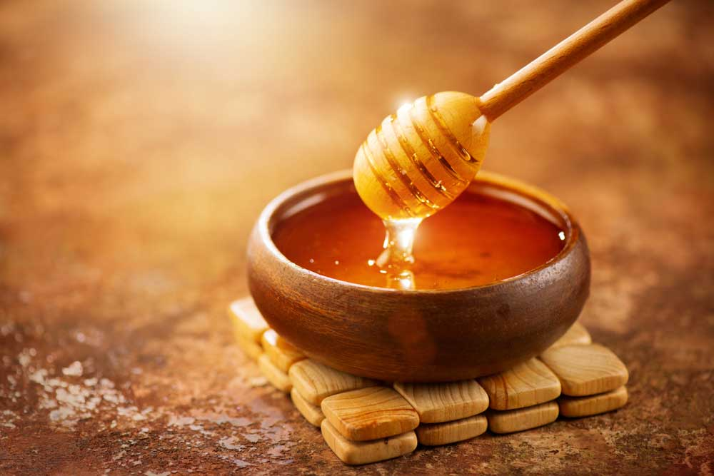 wooden bowl of honey with honey spoon being dipped