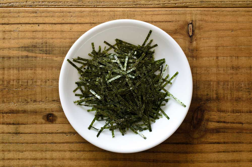 shredded nori in a white bowl on a wooden table
